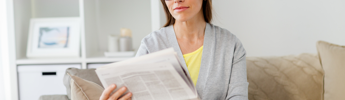 Short banner woman in glasses reading newspaper at home pne85lb