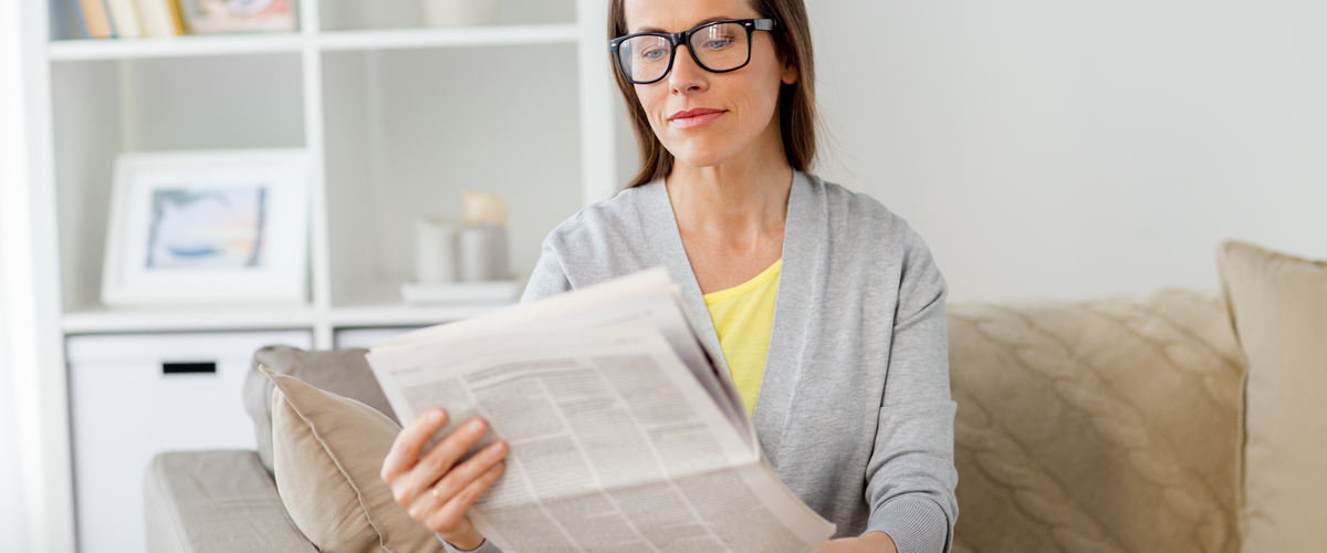Slideshow woman in glasses reading newspaper at home pne85lb