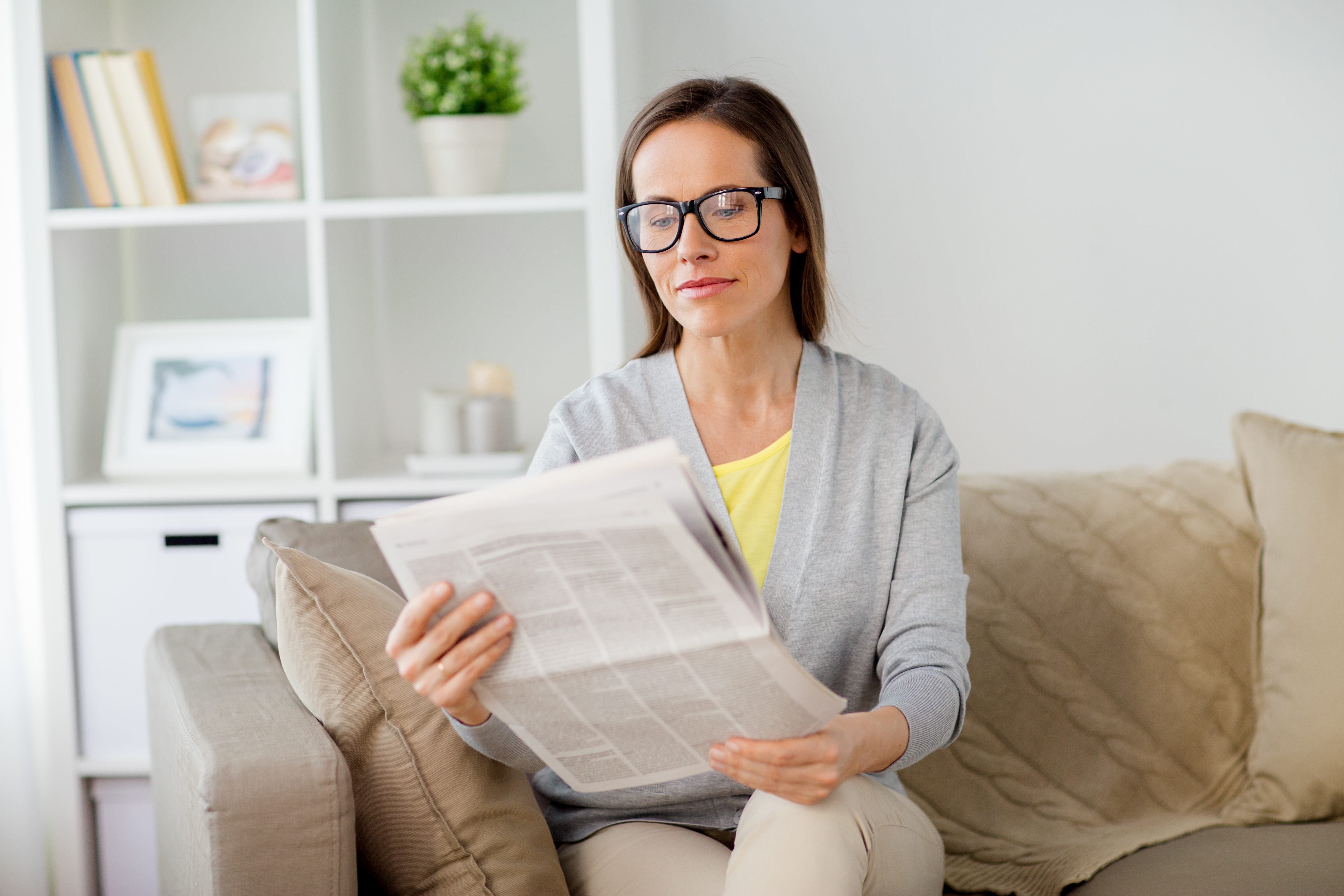 Woman in glasses reading newspaper at home pne85lb