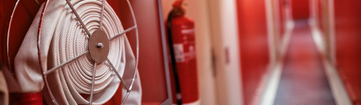 Short banner fire extinguisher and hose reel in hotel corridor p7q39e9