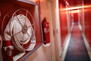 Team fire extinguisher and hose reel in hotel corridor p7q39e9
